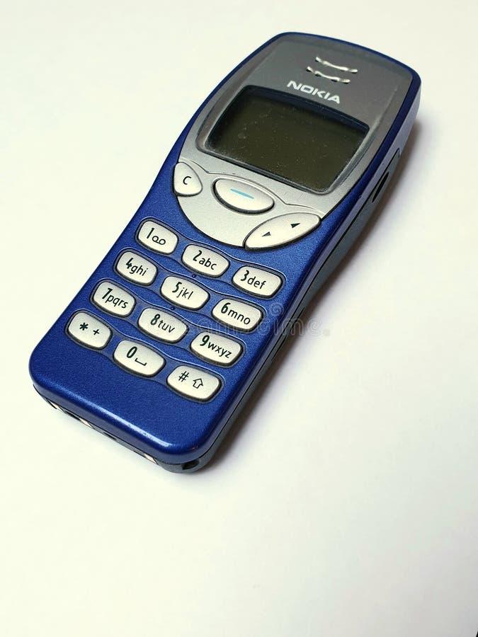 Иконическое голубое Nokia 3310, изолированное на бежевой предпосылке стоковое изображение rf