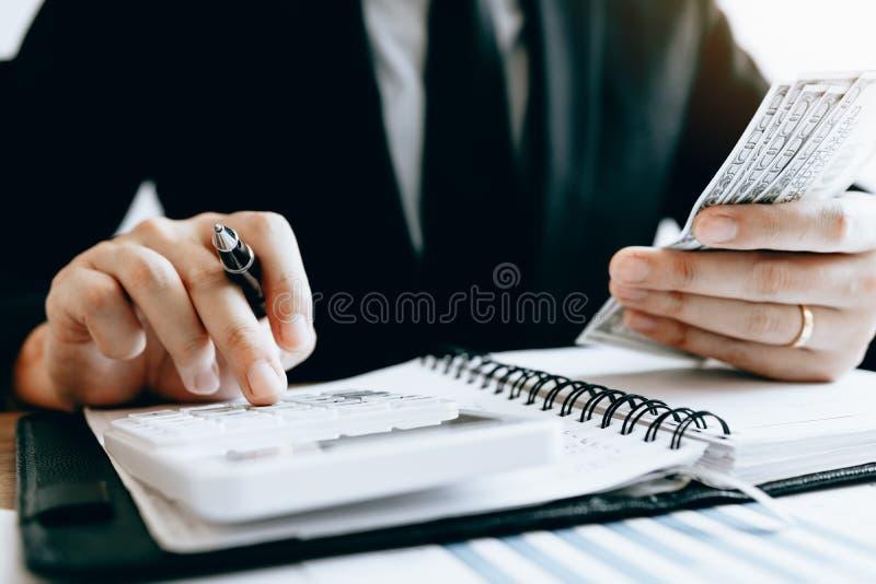 Инвесторы высчитывают на стоимостях инвестирования калькулятора и держат примечания наличных денег в руке стоковое фото
