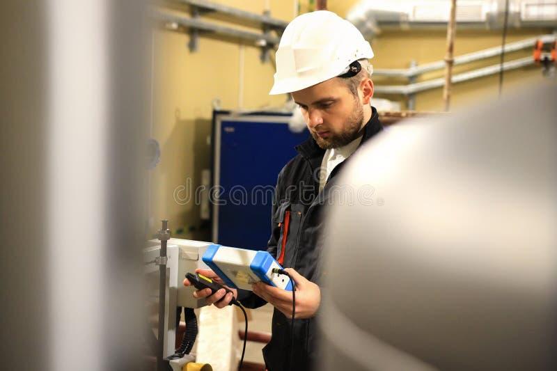 Инженер с тестером измерения на боилере жары стоковые изображения rf