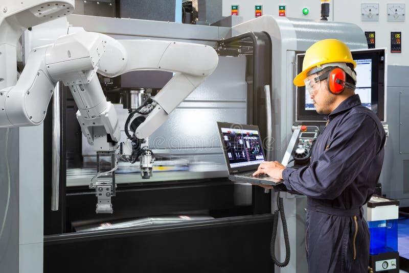 Инженер обслуживания используя руку управлением портативного компьютера автоматическую робототехническую с машиной CNC в умной фа стоковое фото
