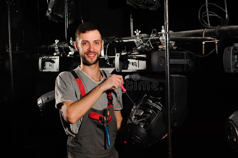 Инженер освещения ремонтирует светлый прибор на этапе стоковое изображение