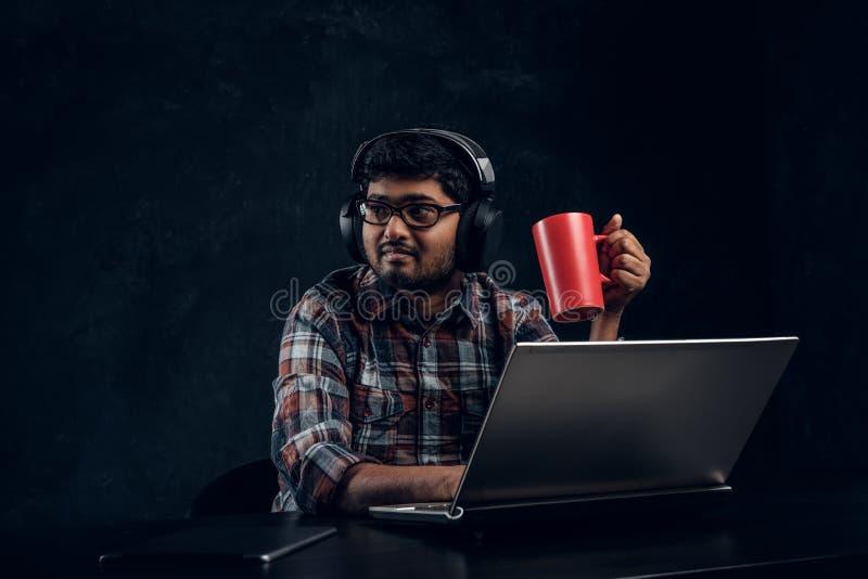 Индийский студент в eyewear и наушниках держа чашку пока сидящ на таблице с ноутбуком стоковые изображения
