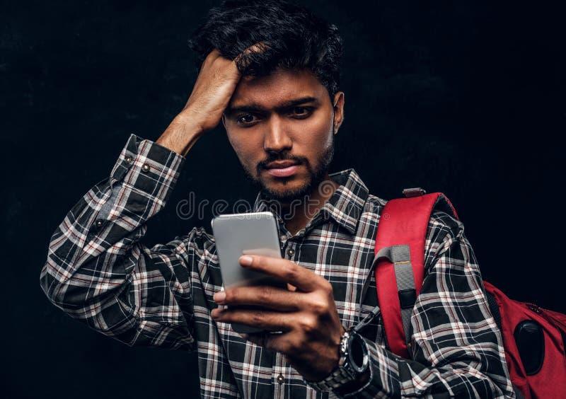 Индийский студент с рюкзаком забыл о том, что-то очень важном и с разочарованным взглядом смотрит его смартфон стоковая фотография rf
