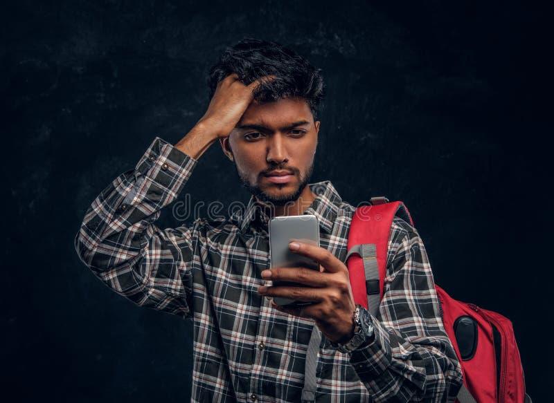 Индийский студент с рюкзаком забыл о том, что-то очень важном и с разочарованным взглядом смотрит его смартфон стоковое изображение rf