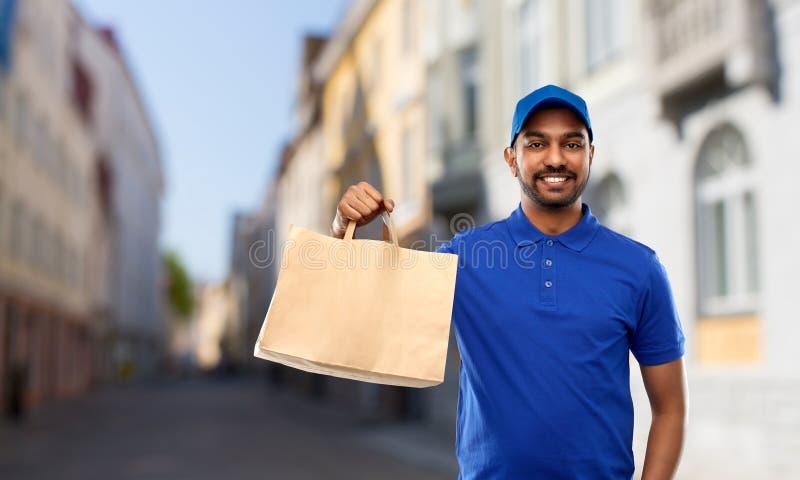 Индийский работник доставляющий покупки на дом с едой в бумажном мешке в городе стоковое фото