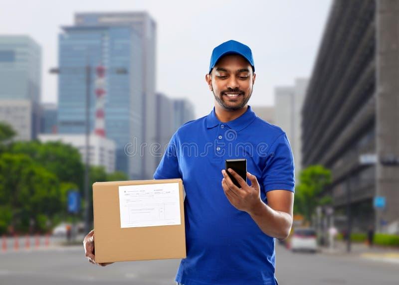 Индийский работник доставляющий покупки на дом с коробкой смартфона и пакета стоковое фото
