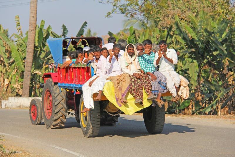 Индия, Hampi, 31-ое января 2018 Индийские люди едут позади открытой тележки, улыбки и волна их руки, говорит здравствуйте стоковое фото