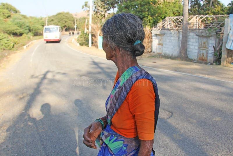 Индия, Hampi, 31-ое января 2018 Старая индийская женщина или старуха в морщинках смотрят дорогу и автобус стоковое изображение rf