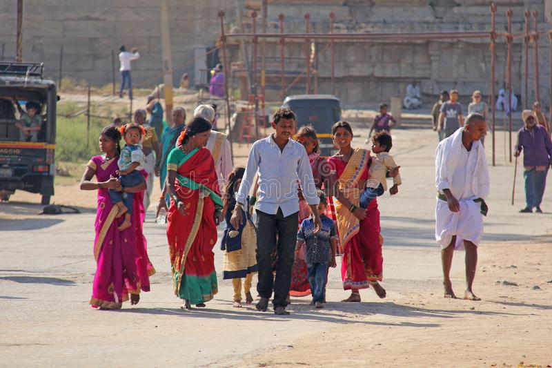 Индия, Hampi, 2-ое февраля 2018 Главная улица деревни Hampi женщины в ярких и красочных сари, людях, детях, группе в составе стоковые фотографии rf