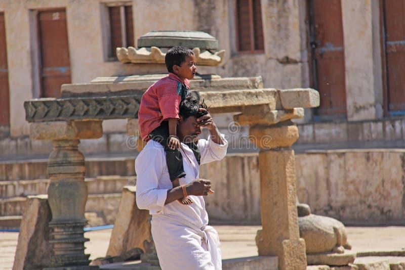 Индия, Hampi, 1-ое февраля 2018 Небольшой индийский мальчик сидит на плечах Папы Папа и сынок Внутри виска Virupaksha стоковые фото
