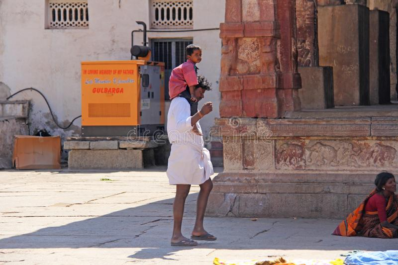 Индия, Hampi, 1-ое февраля 2018 Небольшой индийский мальчик сидит на плечах Папы Папа и сынок Внутри виска Virupaksha стоковая фотография rf