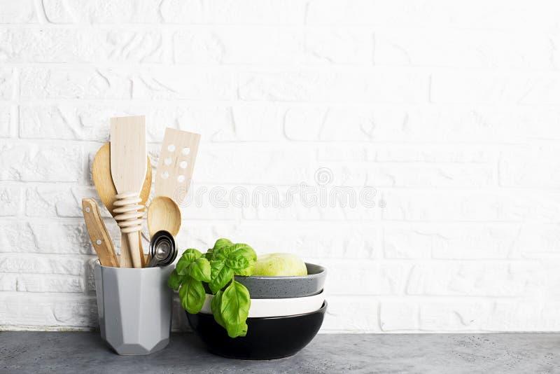 Инструменты кухни, прованское вырезывание boan полка кухни против белой кирпичной стены Свежие базилик и лимон черная белизна стоковая фотография