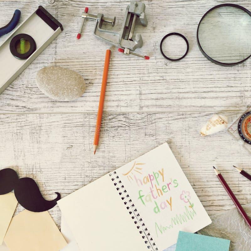 Инструменты отца, черный бумажный усик, лупа, карандаши и приветствуя надпись в тетради на светлом деревянном столе стоковые фотографии rf
