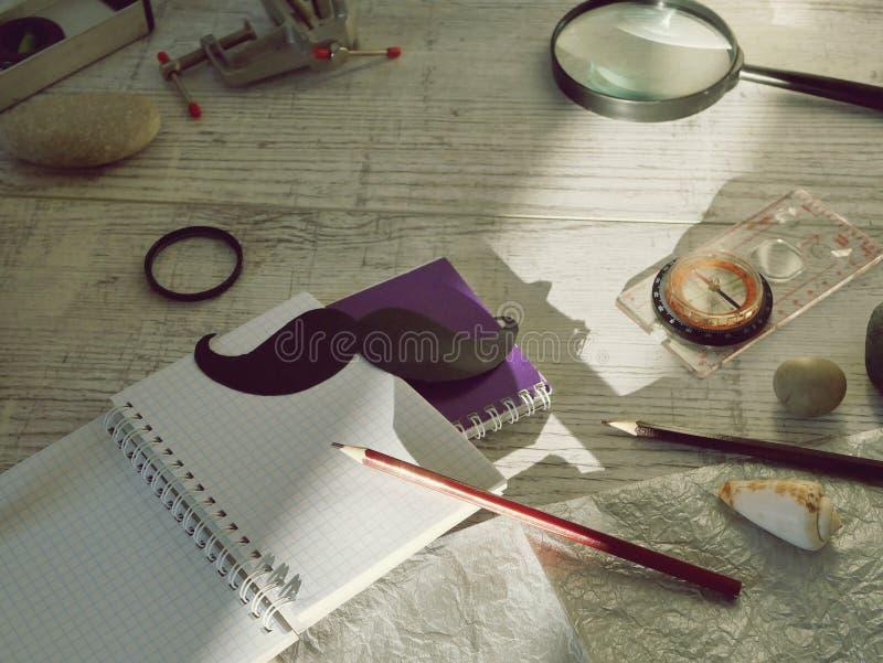Инструменты отца, черный бумажный усик, лупа, карандаши и приветствуя надпись в тетради на светлом деревянном столе стоковые фото
