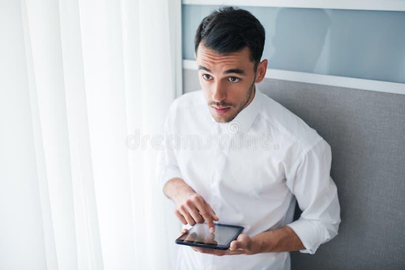 Интересный взгляд сверху красивого бизнесмена работая с прибором, устройства в его руках, стоя перед окном и стоковое фото