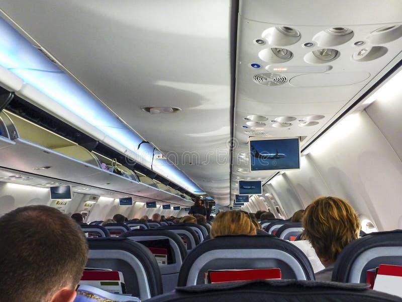 Интерьер самолета принимая с пассажирами усаженными и взглядами перспективы мест и накладных расходов все стоковое фото