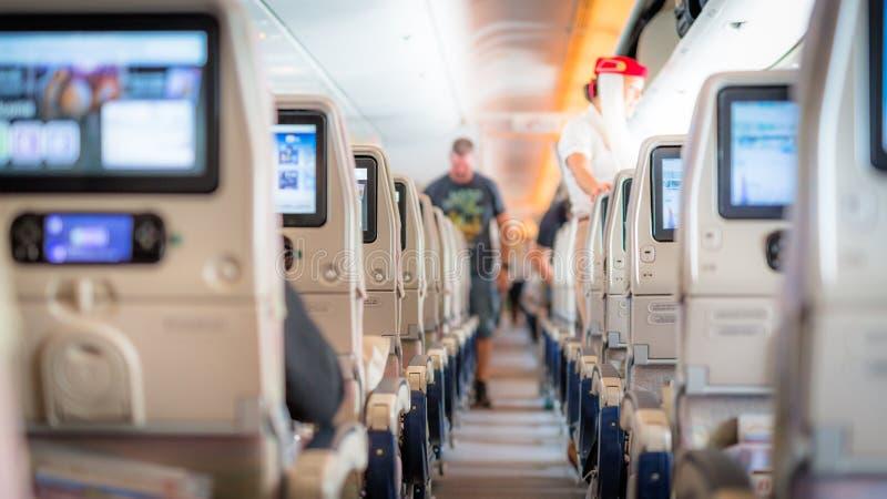 Интерьер самолета с пассажирами на местах ждать к taik  стоковое фото