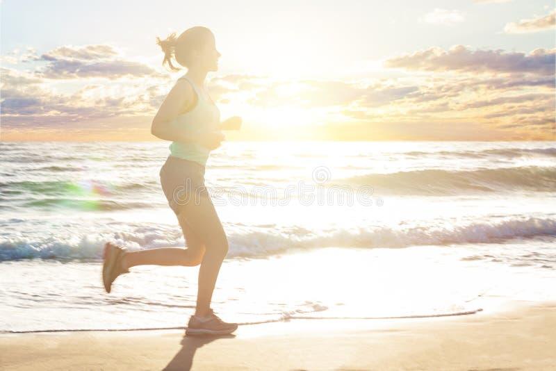 Идущая женщина на пляже моря, движении Девушка jogging на морском побережье в утре лета солнечном Фитнес Здоровый уклад жизни стоковая фотография rf