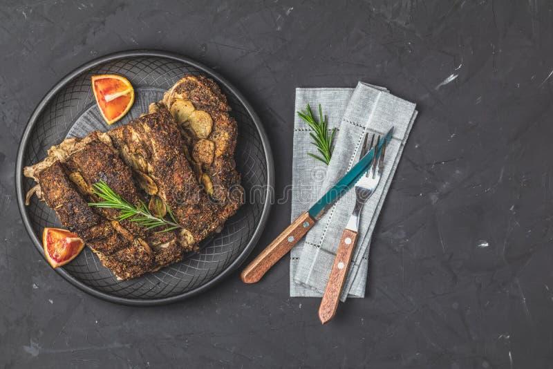 Испеченное мясо свинины жаркого в черной керамической плите с чесноком и специями стоковые изображения rf