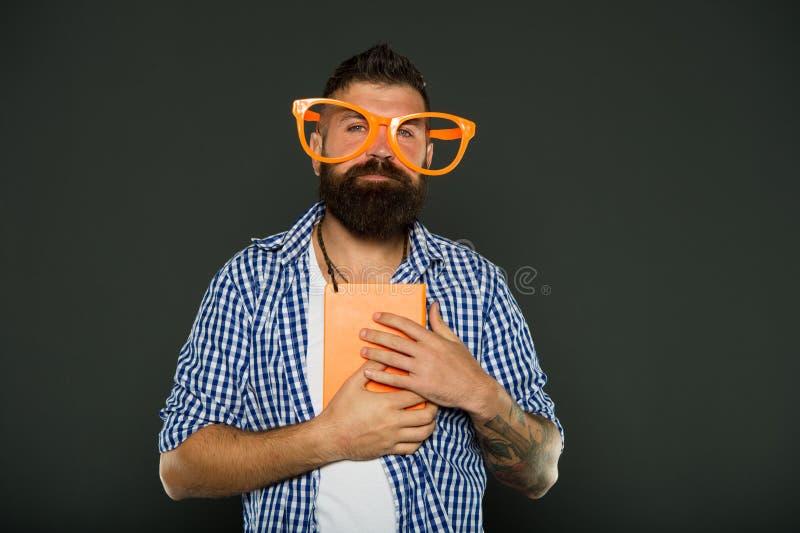 Исследование потеха Eyeglasses бородатого человека хипстера смешные держат блокнот или книгу Прочитайте эту книгу Чувство шуточны стоковые фотографии rf