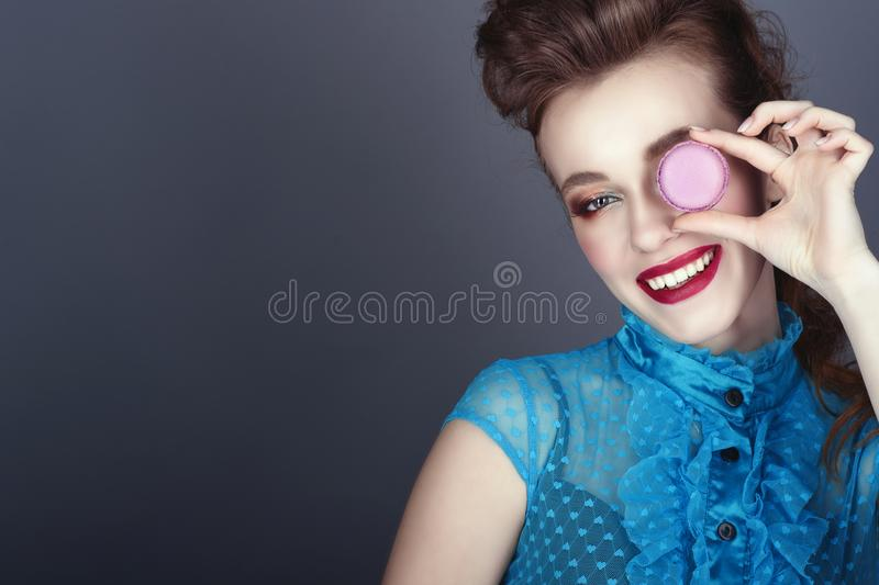 Иeautiful model with creative hairstyle and colourful make up holding violet macaroon in front of her eye and smiling stock photos