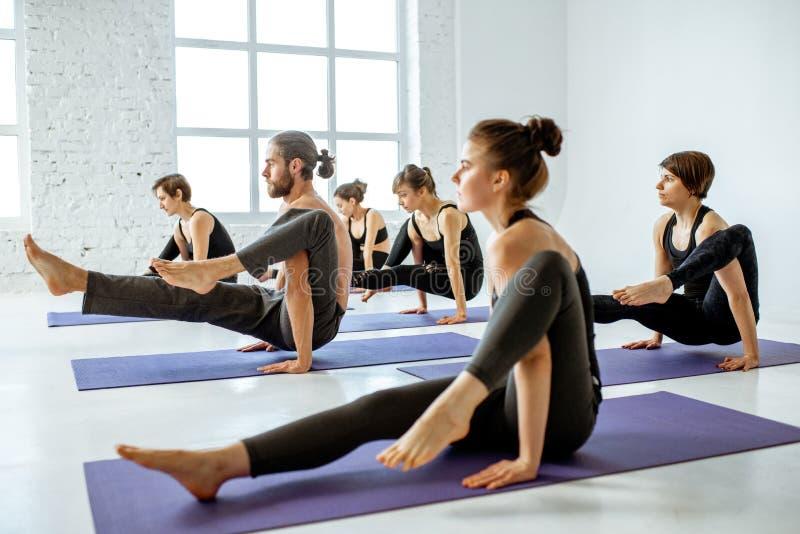 Йога группы людей практикуя внутри помещения стоковые фото