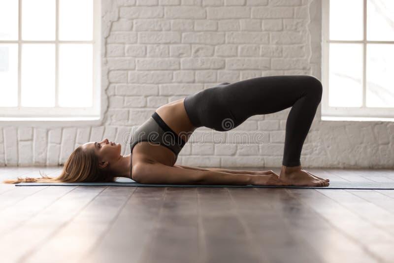 Йога женщины практикуя, тренировка моста Glute, представление pithasana pada dvi стоковое фото