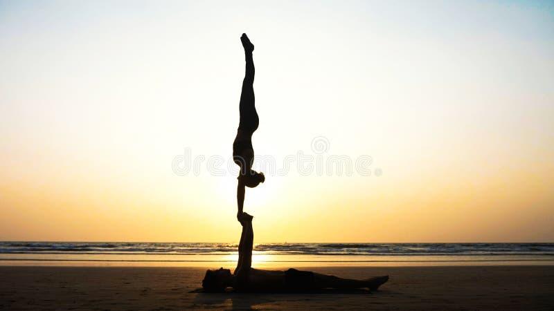 Йога acro подходящих sporty пар практикуя с партнером совместно на песчаном пляже стоковое изображение rf