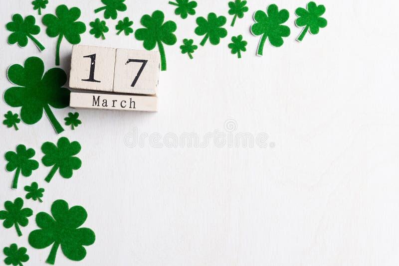 Календарь блока на день St. Patrick, 17-ое марта, с зелеными лист клевера, зеленой водой и биркой бумаги на белой деревянной пред стоковые изображения rf
