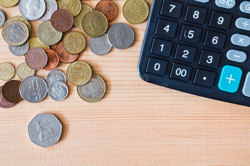 Калькулятор и монетки от различных стран на деревянном столе стоковые фото