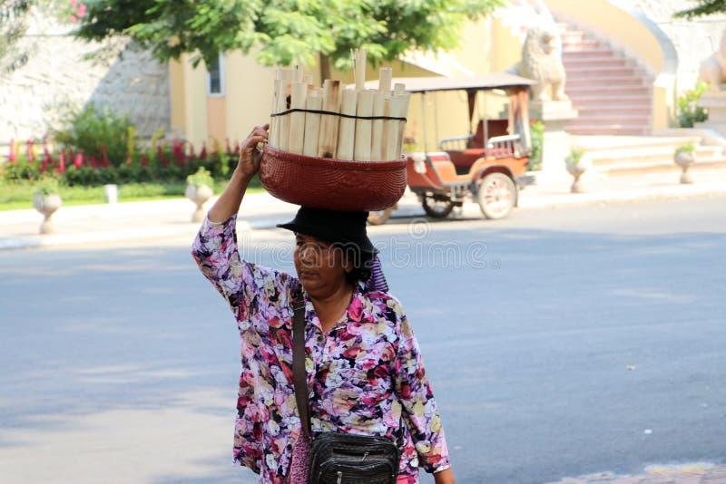 Камбоджийский женский уличный торговец положил испеченную корзину липкого риса выдержанную в молоке кокоса и в раздел бамбукового стоковая фотография rf