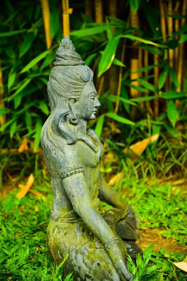 Каменная статуя Будды сидя моля и размышляя для духа души тела разума стоковые изображения