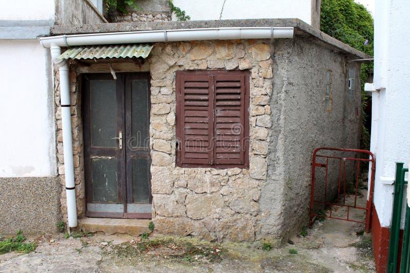 Камень и конкретный небольшой дом с разрушанный треснули деревянные двери и закрытые шторки окна с новой сточной канавой белого м стоковые изображения
