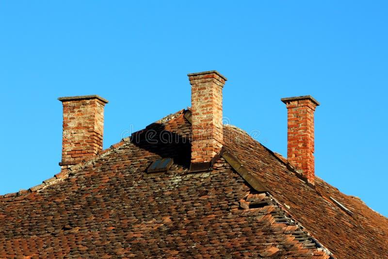 3 камина красных кирпичей поверх старого получившегося отказ дома семьи с треснутыми черепицами и небольшим окном крыши стоковые изображения rf