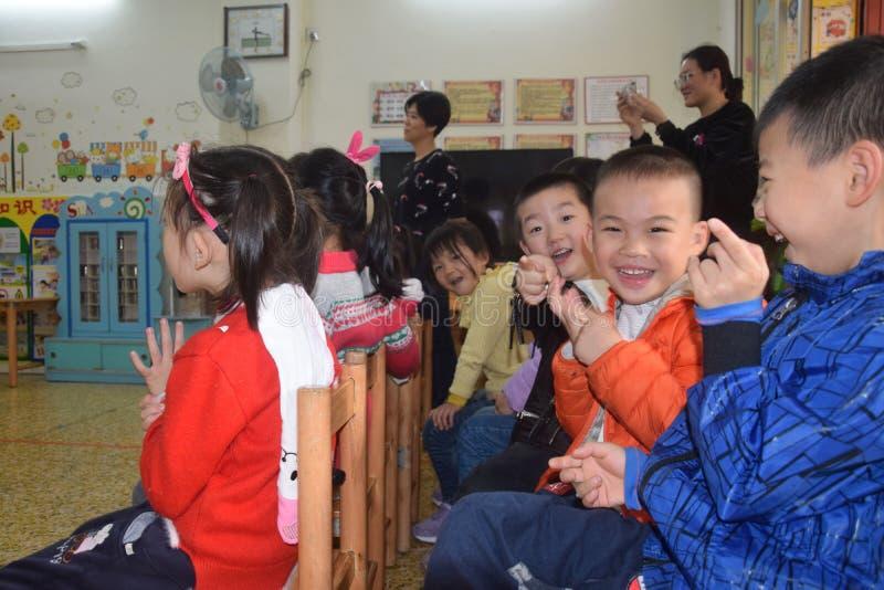 КАНТОН, †КИТАЯ «ОКОЛО МАРТ 2019: Усмехаясь мальчики наблюдая представление их одноклассников в детском саде стоковые изображения rf