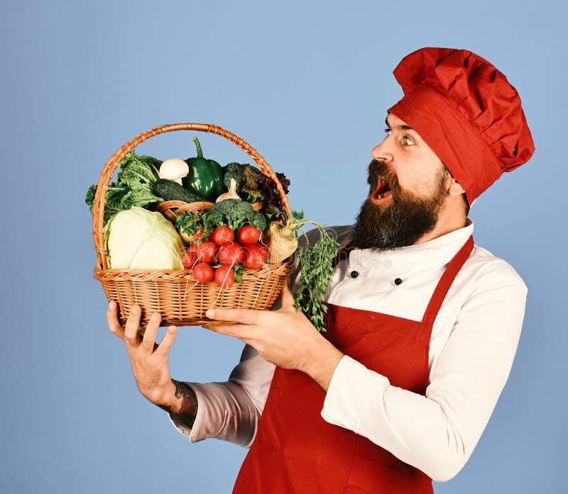 Кашевар с сотрясенной стороной в бургундской форме держит овощи стоковая фотография