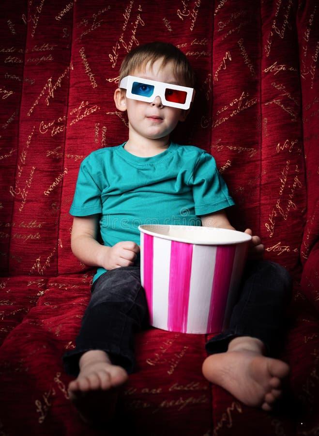 Кино детей: мальчик смотрит фильм в стеклах 3D на красной софе и ест попкорн стоковые фотографии rf