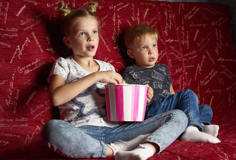 Кино детей: Девушка и мальчик смотрят фильм дома на большой красной софе в темноте и едят попкорн стоковые фото