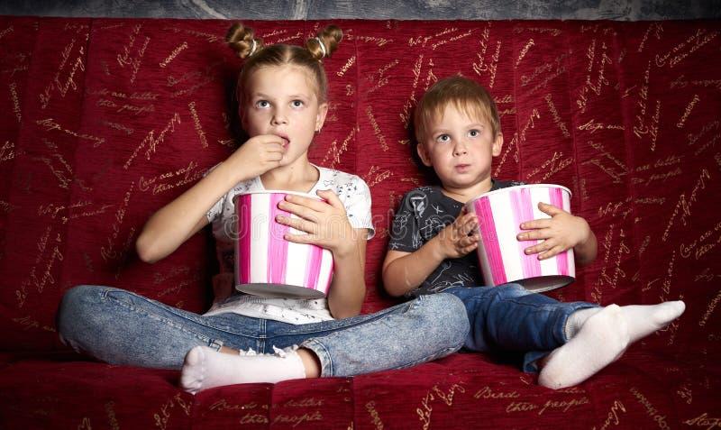 Кино детей: Девушка и мальчик смотрят фильм дома на большой красной софе в темноте и едят попкорн стоковая фотография rf