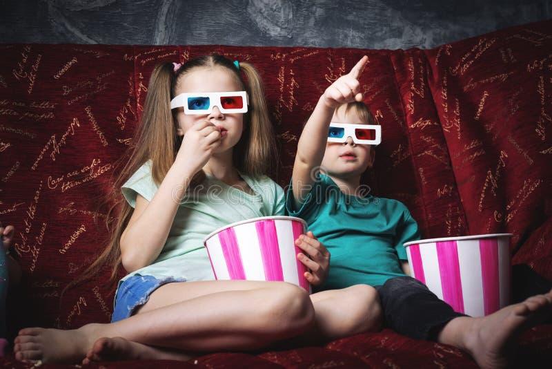 Кино детей: Дети сидят на красной софе и смотрят фильм 3D стоковые изображения
