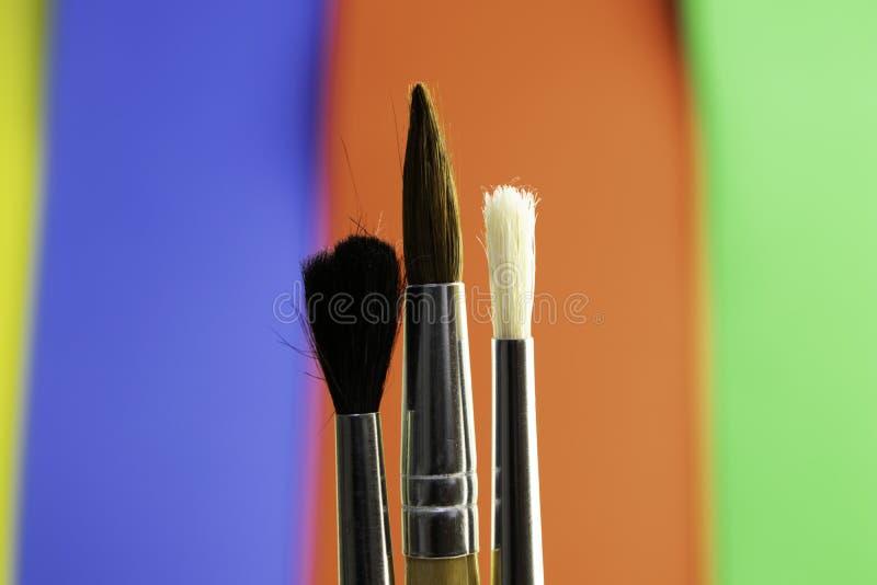 3 кисти на предпосылке запачканной цветом стоковое изображение
