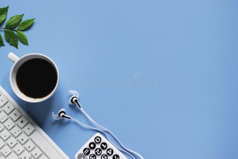 Клавиатура, тетрадь, ручка, или объект взгляда сверху для концепции канцелярские товара на голубой предпосылке стоковые фото