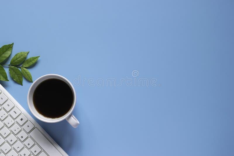 Клавиатура, тетрадь, ручка, или объект взгляда сверху для концепции канцелярские товара на голубой предпосылке стоковая фотография rf