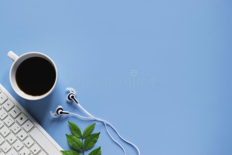 Клавиатура, тетрадь, ручка, или объект взгляда сверху для концепции канцелярские товара на голубой предпосылке стоковая фотография