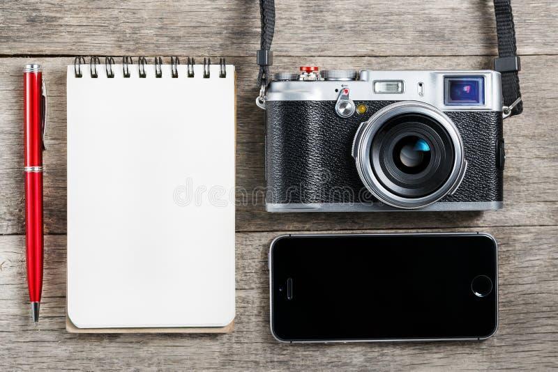 Классическая камера с пустой страницей блокнота и красная ручка на сером деревянном, винтажном столе с телефоном стоковая фотография