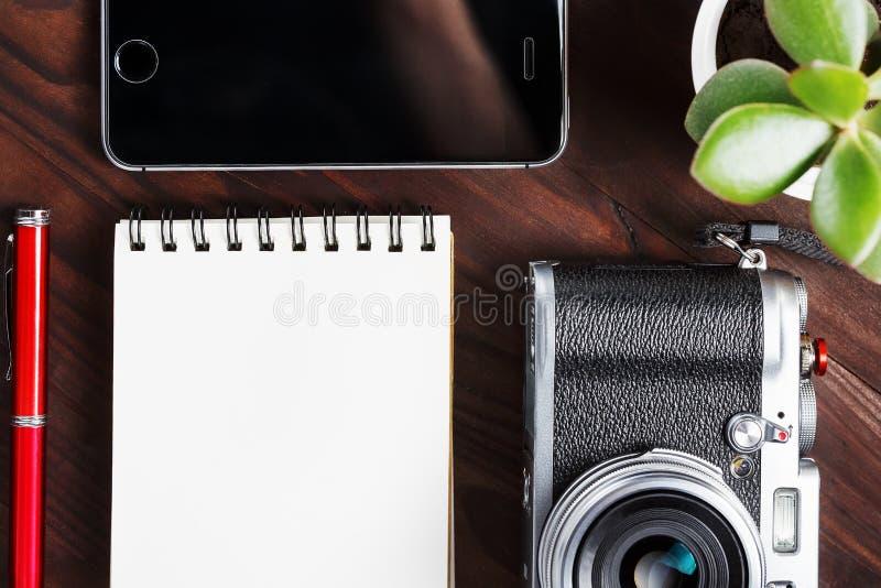 Классическая камера с пустой страницей блокнота и красная ручка на темном коричневом деревянном столе, винтажной таблице с телефо стоковое фото