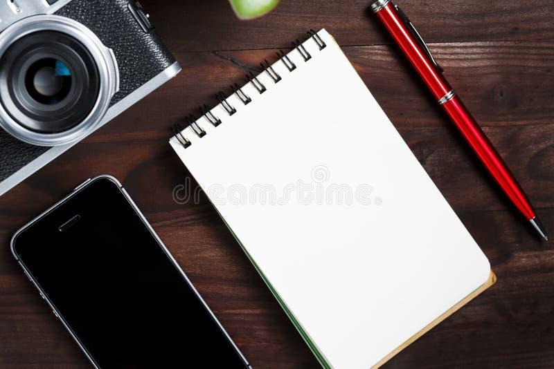 Классическая камера с пустой страницей блокнота и красная ручка на темном коричневом деревянном столе, винтажной таблице с телефо стоковые изображения