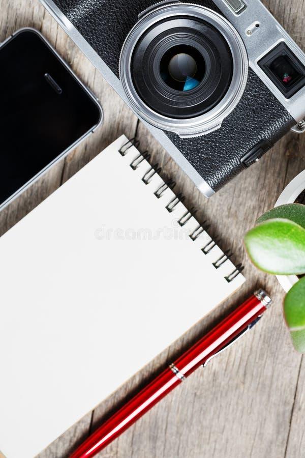 Классическая камера с пустой страницей блокнота и красная ручка на сером деревянном, винтажном столе с телефоном стоковое изображение rf