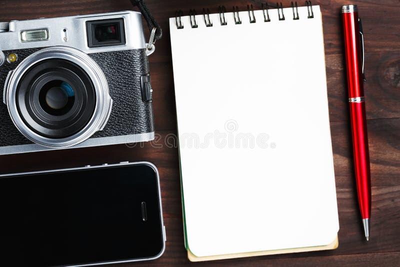 Классическая камера с пустой страницей блокнота и красная ручка на темном коричневом деревянном столе, винтажной таблице с телефо стоковые изображения rf