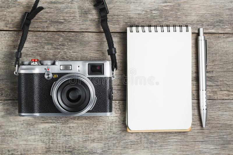 Классическая камера с пустой страницей блокнота и серая ручка на сером деревянном, винтажном столе стоковое фото